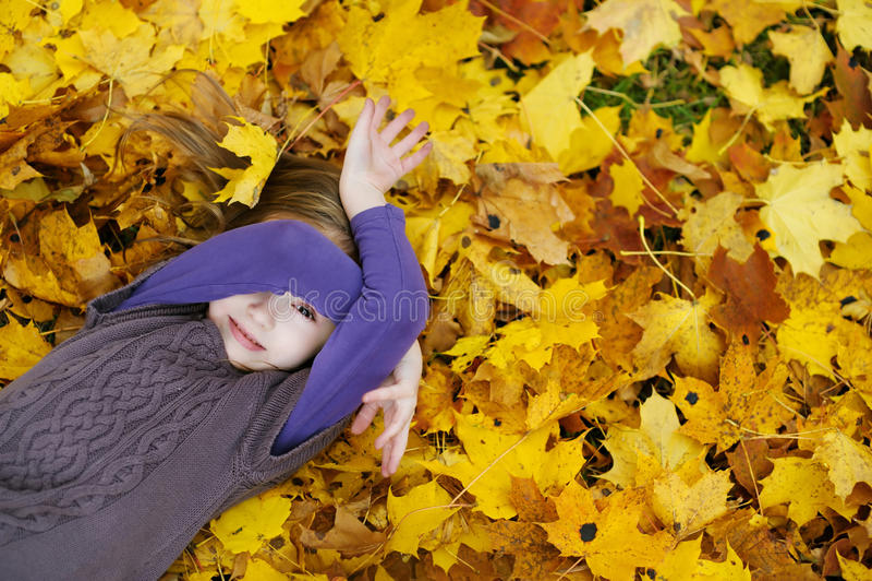 Λατρευτό μικρό κορίτσι που βάζει στα χρυσά φύλλα σφενδάμου στοκ εικόνες