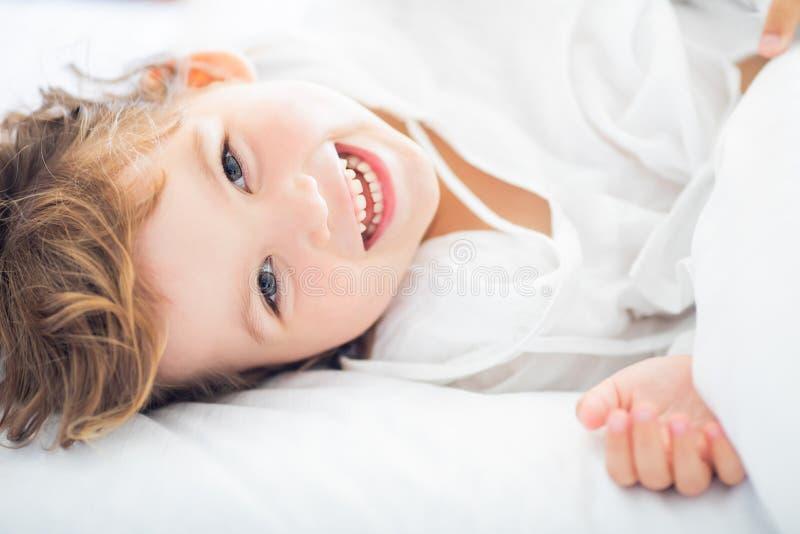Λατρευτό μικρό κορίτσι που βρίσκεται στο κρεβάτι και που χαμογελά στα ξημερώματα στοκ εικόνες