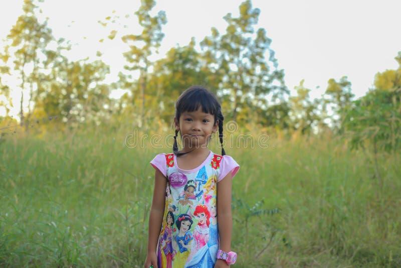 Λατρευτό μικρό κορίτσι που γελά σε ένα λιβάδι - ευτυχές κορίτσι στο ηλιοβασίλεμα στοκ εικόνα
