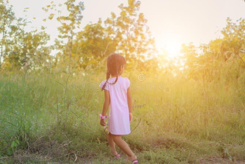 Λατρευτό μικρό κορίτσι που γελά σε ένα λιβάδι - ευτυχές κορίτσι στο ηλιοβασίλεμα στοκ φωτογραφίες
