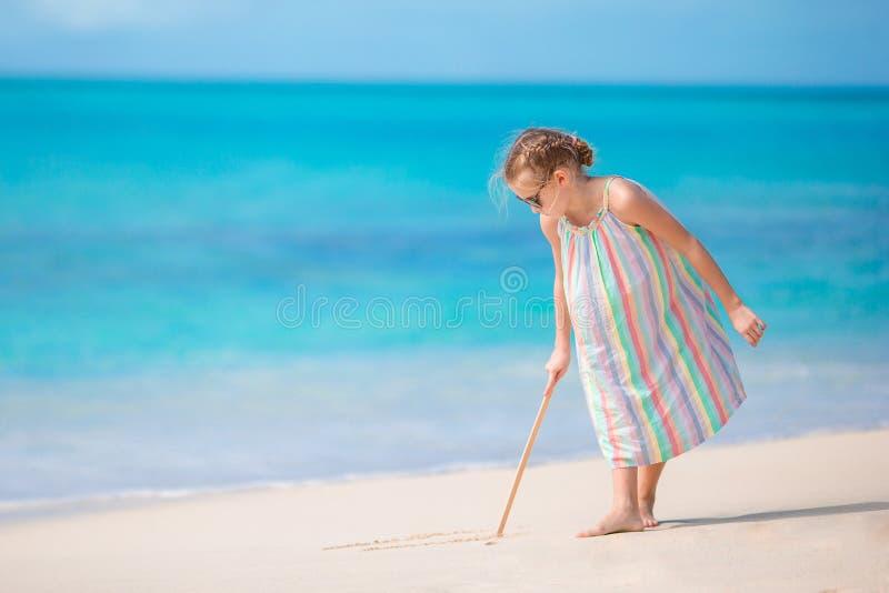 Λατρευτό μικρό κορίτσι στην παραλία κατά τη διάρκεια των θερινών διακοπών που επισύρει την προσοχή στην άμμο στοκ εικόνες