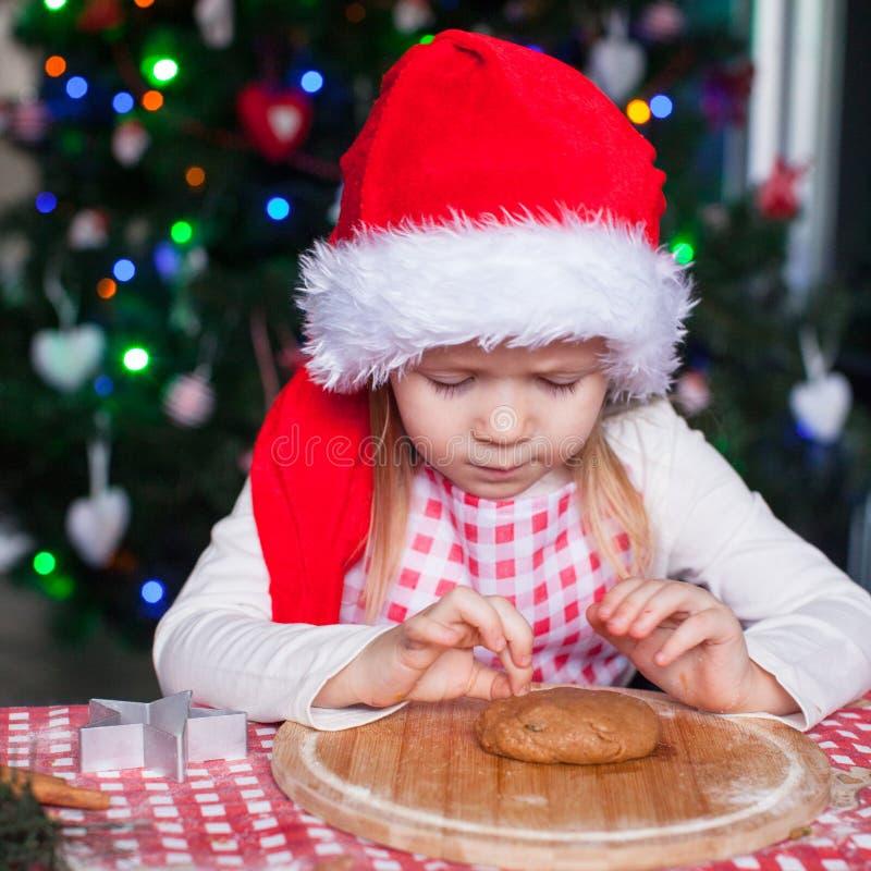 Λατρευτό μικρό κορίτσι στο καπέλο Santa που τρώει τη ζύμη στοκ εικόνα με δικαίωμα ελεύθερης χρήσης