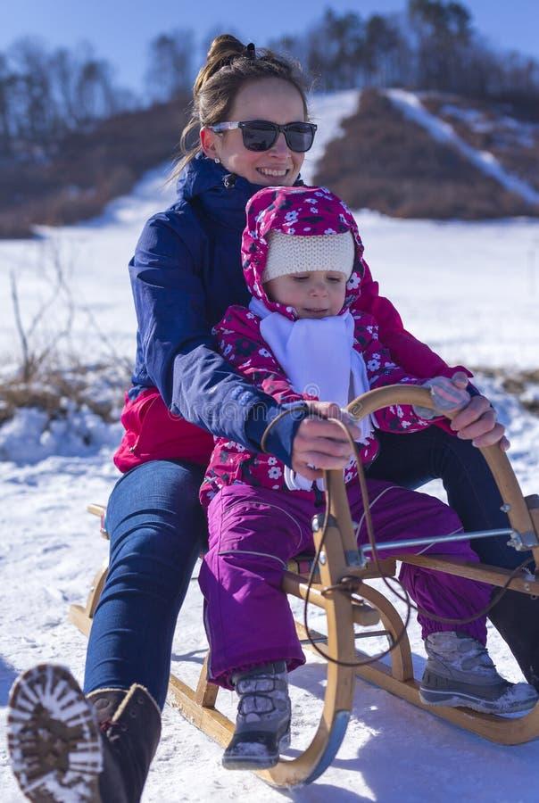 Λατρευτό μωρό σε ένα άσπρο χιόνι στο θερμό κοστούμι που εγκαθιστά στο χιόνι στοκ εικόνα