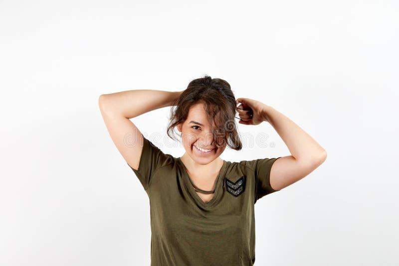 Λατρευτό νέο μαυρισμένο θηλυκό που κάνει ponytail τη στάση πέρα από το άσπρο υπόβαθρο στούντιο στοκ εικόνες
