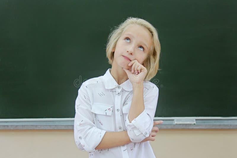 Λατρευτό ξανθό κορίτσι παιδιών στοχαστικό σε μια τάξη κοντά σε έναν πίνακα κιμωλίας Το παιδί στρέφεται και προσεκτικός θυμάται στοκ φωτογραφία με δικαίωμα ελεύθερης χρήσης