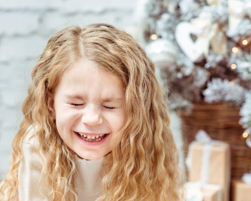 Λατρευτό ξανθό μικρό κορίτσι με τις ιδιαίτερες προσοχές που γελά, Χριστούγεννα στοκ φωτογραφία