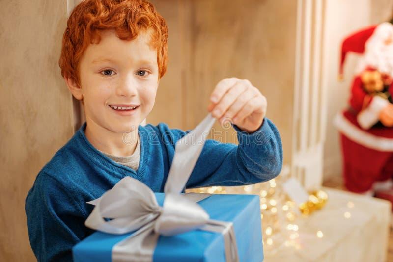 Λατρευτό παιδί που χαμογελά στη κάμερα ανοίγοντας το παρόν του στοκ φωτογραφίες με δικαίωμα ελεύθερης χρήσης