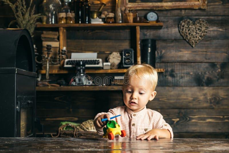 Λατρευτό παιχνίδι μικρών παιδιών με το ελικόπτερο παιχνιδιών στον παιδικό σταθμό Παιδικός σταθμός και βρεφικός σταθμός στοκ φωτογραφία με δικαίωμα ελεύθερης χρήσης
