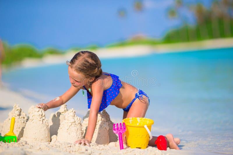 Λατρευτό παιχνίδι μικρών κοριτσιών με τα παιχνίδια παραλιών στοκ φωτογραφία