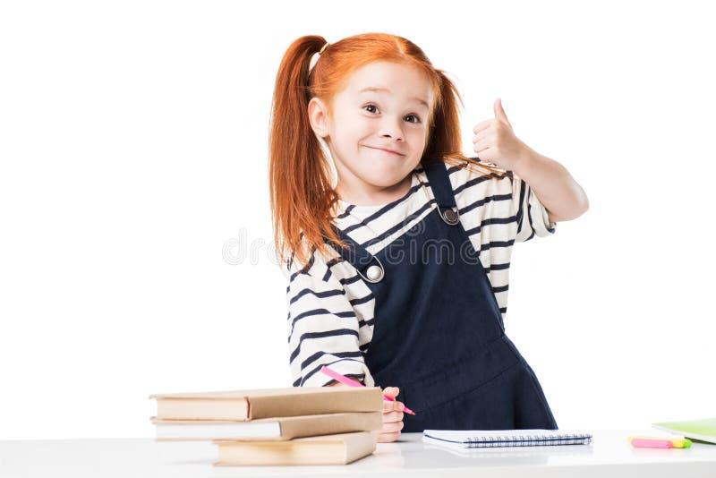 λατρευτό σχέδιο μαθητριών χαμόγελου redhead με τις μάνδρες ακρών πιλήματος και παρουσίαση αντίχειρα στοκ φωτογραφία με δικαίωμα ελεύθερης χρήσης