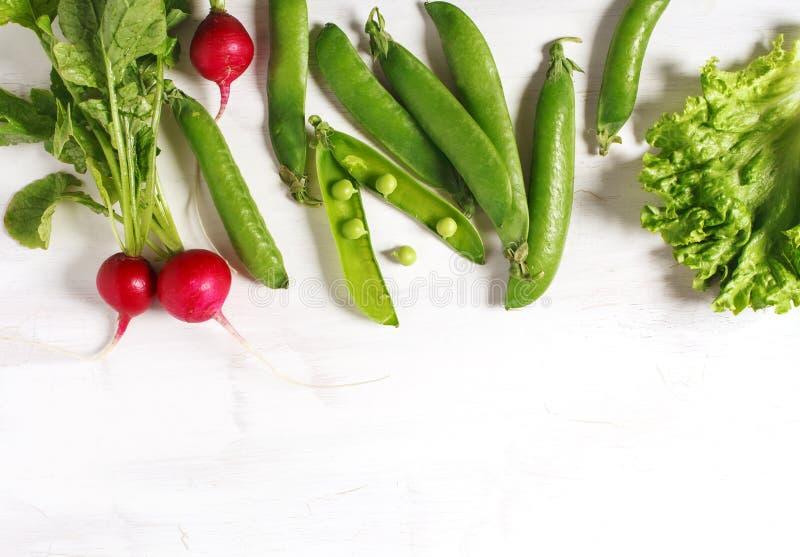 Λαχανικά άνοιξη στο άσπρο ξύλινο υπόβαθρο με το διάστημα αντιγράφων Ραδίκι, πράσινα μπιζέλια και πράσινη σαλάτα στοκ εικόνα