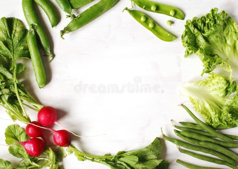 Λαχανικά άνοιξη στο άσπρο ξύλινο υπόβαθρο με το διάστημα αντιγράφων Ραδίκι, πράσινα μπιζέλια, πράσινα φασόλια και πράσινη σαλάτα στοκ εικόνες