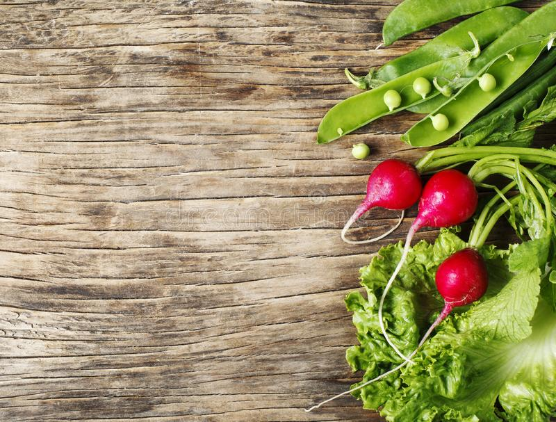 Λαχανικά άνοιξη στο ξύλινο υπόβαθρο με το διάστημα αντιγράφων Ραδίκι, πράσινα μπιζέλια και πράσινη σαλάτα - φρέσκια συγκομιδή στοκ εικόνα