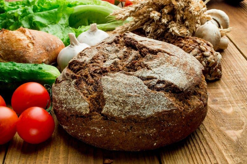 Λαχανικά, ντομάτες, αυγά, ψωμί σε έναν ξύλινο πίνακα στοκ εικόνες