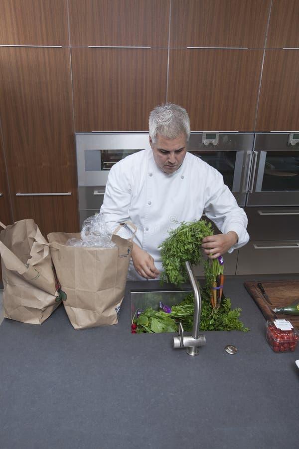 Λαχανικά πλύσης αρχιμαγείρων στο νεροχύτη κουζινών στοκ εικόνες