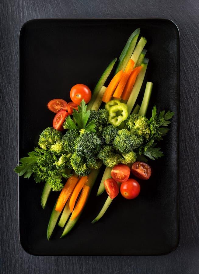 λαχανικά σε ένα μαύρο πιάτο στοκ εικόνα