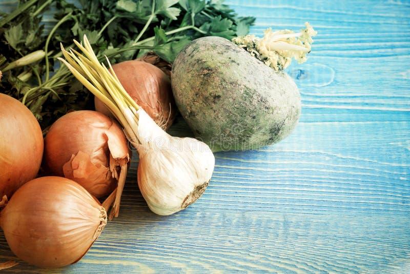 Λαχανικά σε ένα ξύλινο υπόβαθρο, ένα αναδρομικό ύφος, κρεμμύδια, πράσινα, σκόρδο, ραδίκι στοκ εικόνες