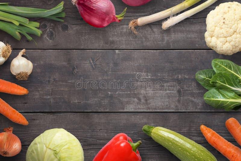 Λαχανικά στη μαύρη ξύλινη επιφάνεια με το διάστημα αντιγράφων στη μέση στοκ εικόνες