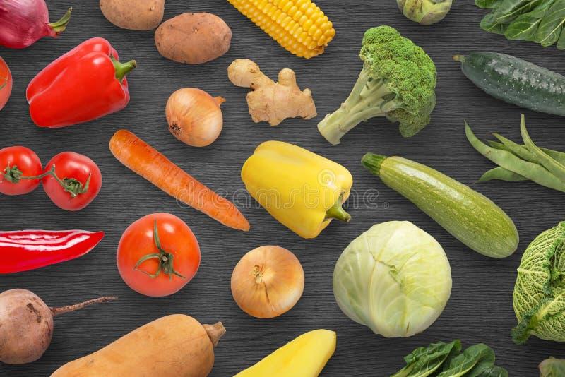 Λαχανικά στη μαύρη ξύλινη επιφάνεια με το διάστημα αντιγράφων στη μέση στοκ φωτογραφία
