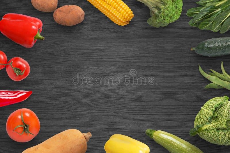 Λαχανικά στη μαύρη ξύλινη επιφάνεια με το διάστημα αντιγράφων στη μέση στοκ φωτογραφίες