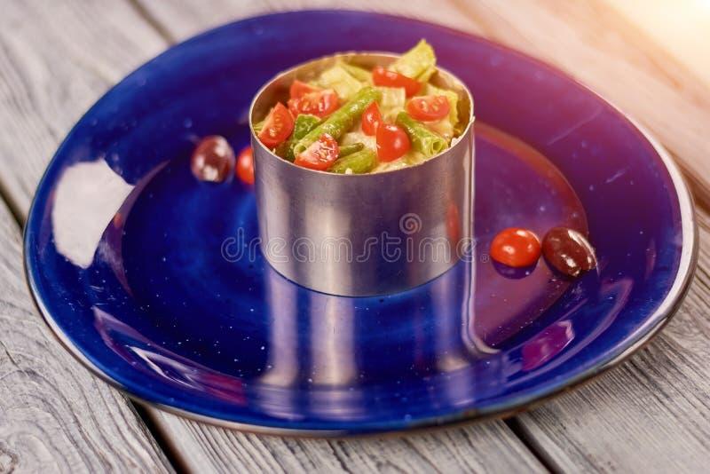 Λαχανικά στο κύπελλο χάλυβα στο πιάτο στοκ φωτογραφία