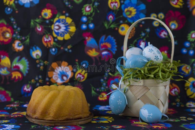Λαϊκή διακόσμηση Πάσχας ύφους με τα άσπρα και μπλε αυγά στο χρωματισμένο υφαντικό υπόβαθρο στοκ φωτογραφίες