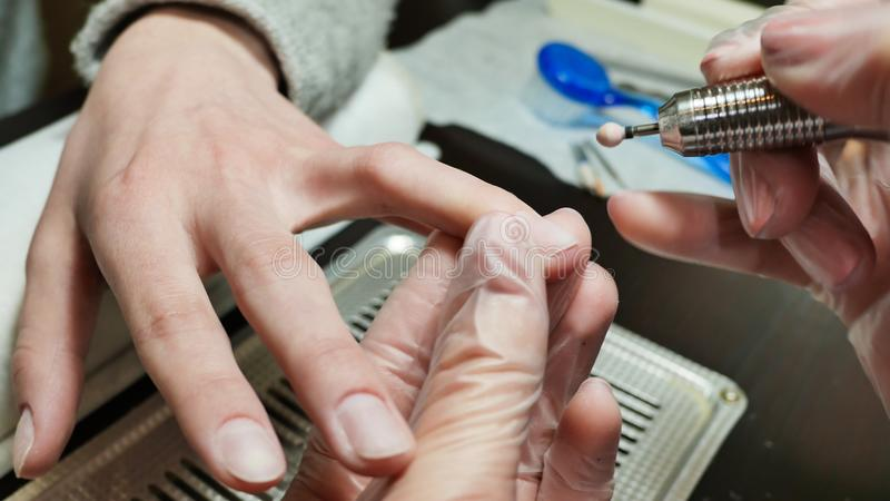 Λείανση μιας επιδερμίδας και δευτερευόντων κυλίνδρων Χέρια γυναικών ` s στις διαδικασίες μανικιούρ στοκ εικόνα με δικαίωμα ελεύθερης χρήσης