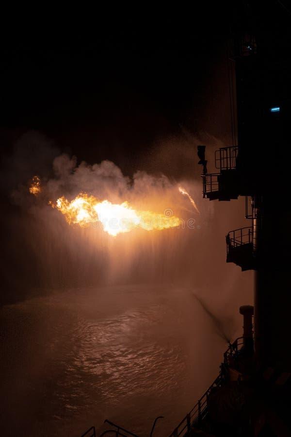 Λειτουργία ελέγχου γεώτρησης κοιτασμάτων για την πυρόσβεση πετρελαίου και αερίου Η καύση τεράστιας φλόγας αερίου ελέγχεται από το στοκ φωτογραφία