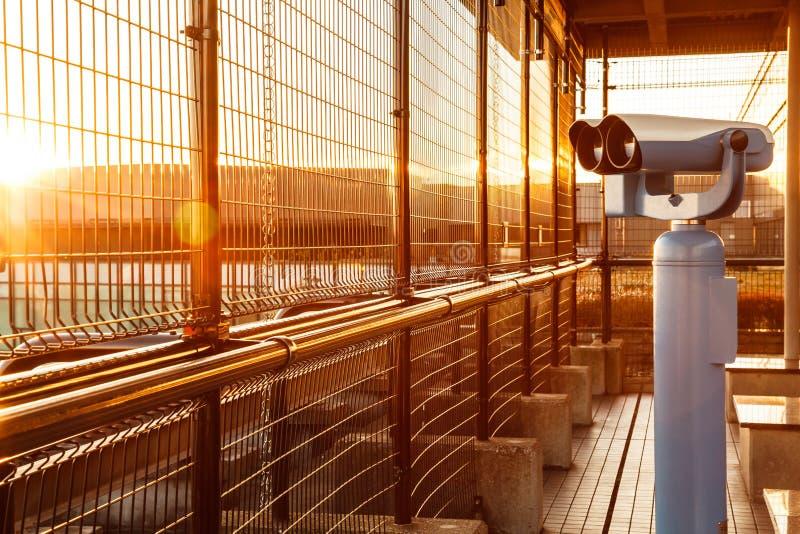 Λειτουργούν με κέρματα διόπτρες ή τηλεσκόπιο στο χρυσό φως πυράκτωσης πρωινού για τους τουρίστες για να παρατηρήσουν τις απογειώσ στοκ εικόνα με δικαίωμα ελεύθερης χρήσης