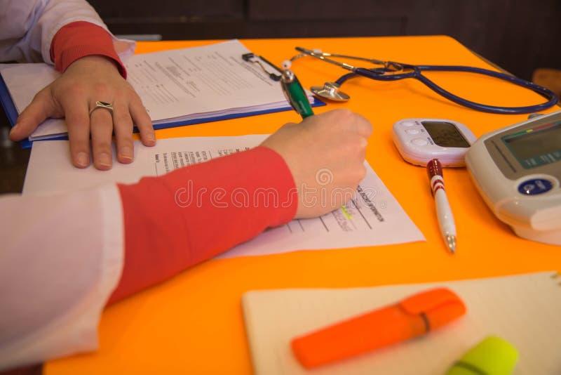 Λειτουργώντας πίνακας του γιατρού ιατρικής r Ο γιατρός κάθεται σε ένα ιατρικό γραφείο στην κλινική και γράφει το ιατρικό ιστορικό στοκ φωτογραφία