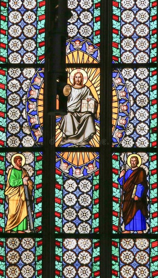Λεκιασμένο γυαλί - Ιησούς που κρατούν την ιερή Βίβλο και Άγιοι στοκ εικόνα