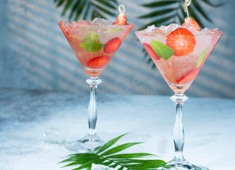Λεμονάδα φραουλών ή οινοπνευματώδες κοκτέιλ με τα φύλλα σόδας και μεντών σιροπιού πάγου στον πίνακα φραγμών στοκ εικόνες