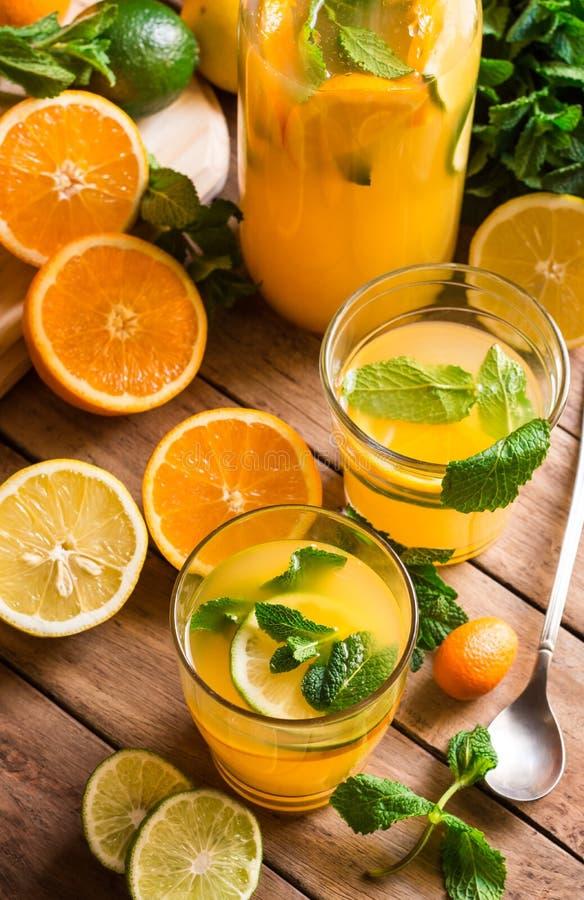 Λεμονάδα εσπεριδοειδών από τη φρέσκια μέντα πορτοκαλιών ασβέστη στα γυαλιά και μπουκάλι, φρούτα περικοπών στον πίνακα κουζινών στοκ εικόνα