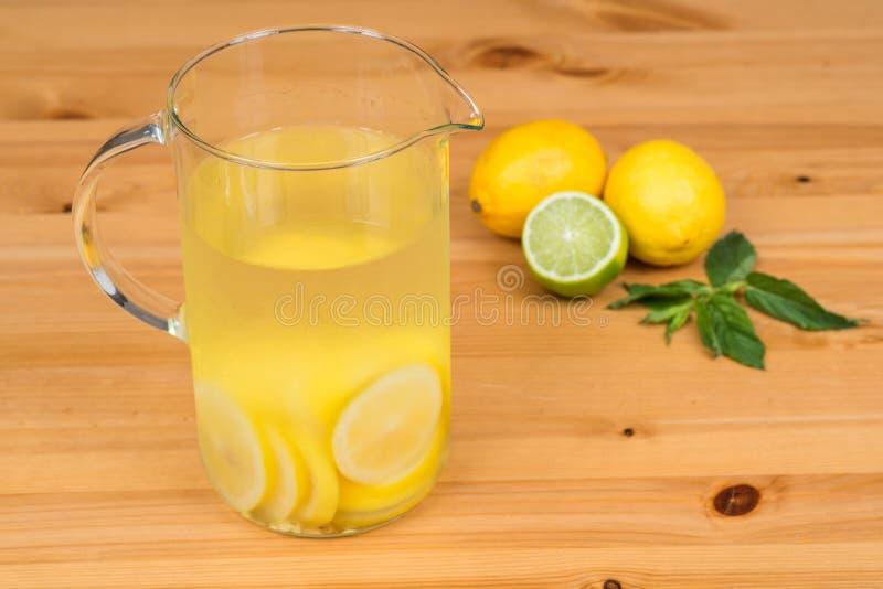 Λεμονάδα με δύο λεμόνια, έναν ασβέστη και μια μέντα, ξύλινο υπόβαθρο στοκ φωτογραφία