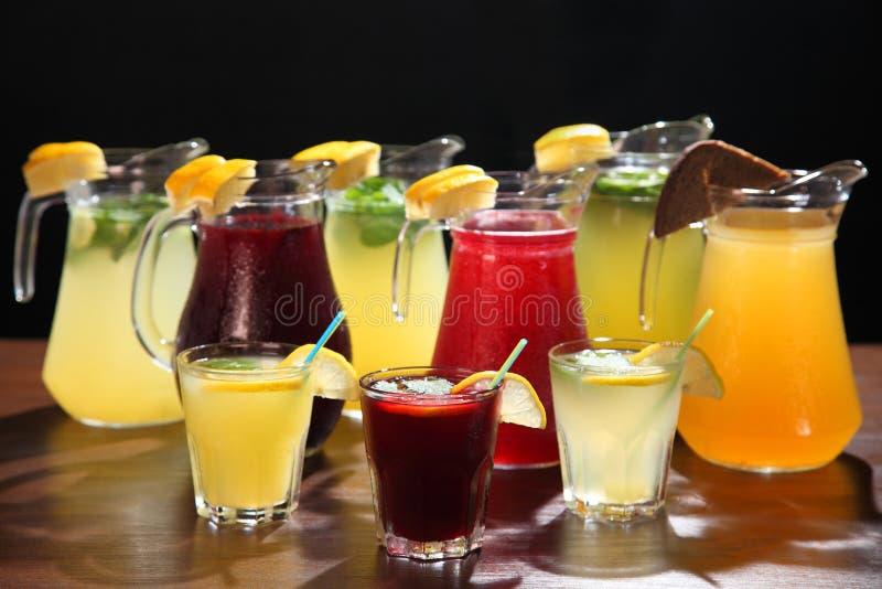 Λεμονάδα στην κανάτα και λεμόνια με τη μέντα στον πίνακα εσωτερικό Δίψα απόσβεσης και αναζωογονώντας ποτά στοκ εικόνα