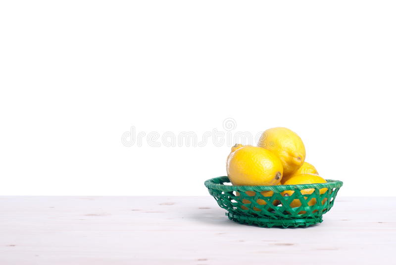 Λεμόνια σε ένα φωτεινό καλάθι στην επιτραπέζια πλάγια όψη της απομόνωσης στοκ φωτογραφία με δικαίωμα ελεύθερης χρήσης