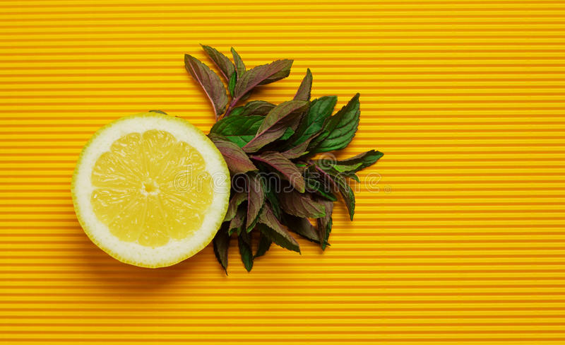 Λεμόνι και μέντα στο κίτρινο υπόβαθρο στοκ φωτογραφία με δικαίωμα ελεύθερης χρήσης