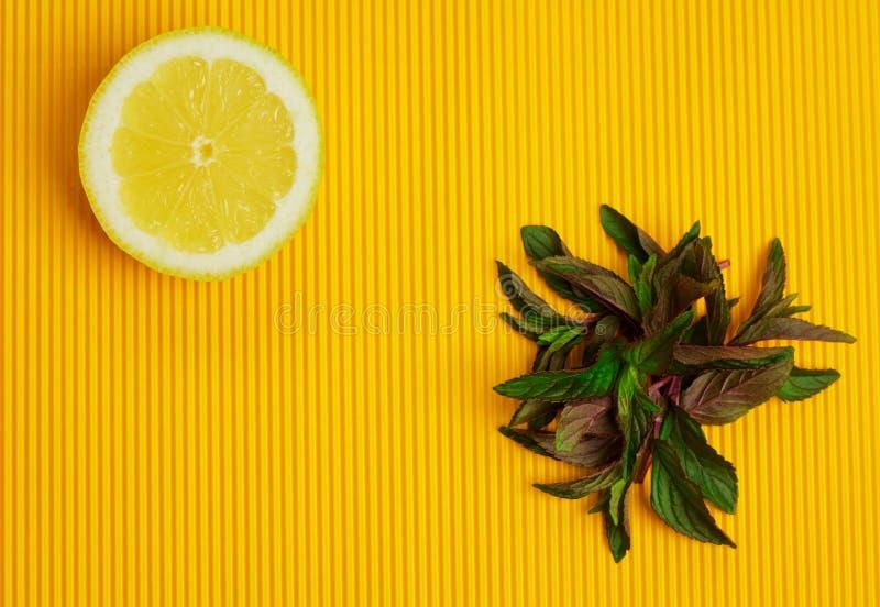 Λεμόνι και μέντα στο κίτρινο υπόβαθρο στοκ εικόνες