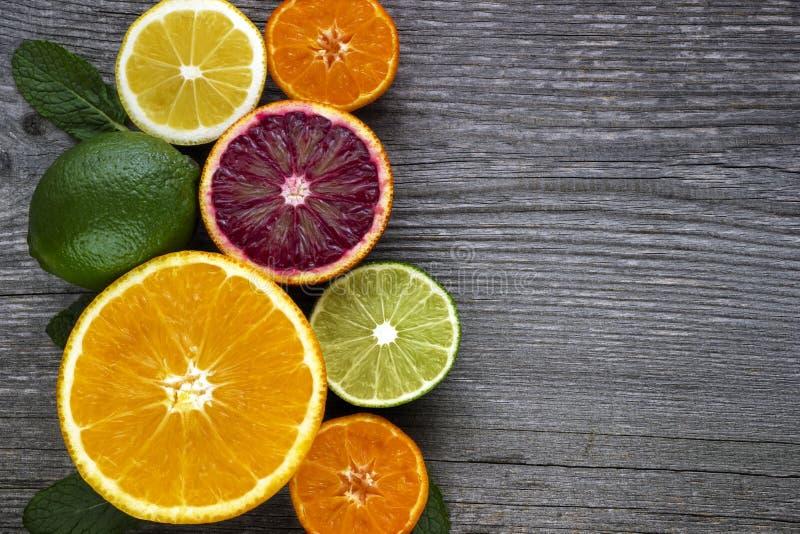 Λεμόνι, κόκκινο πορτοκάλι, πορτοκάλι, γκρέιπφρουτ, ασβέστης στον παλαιό ξύλινο πίνακα στοκ εικόνα