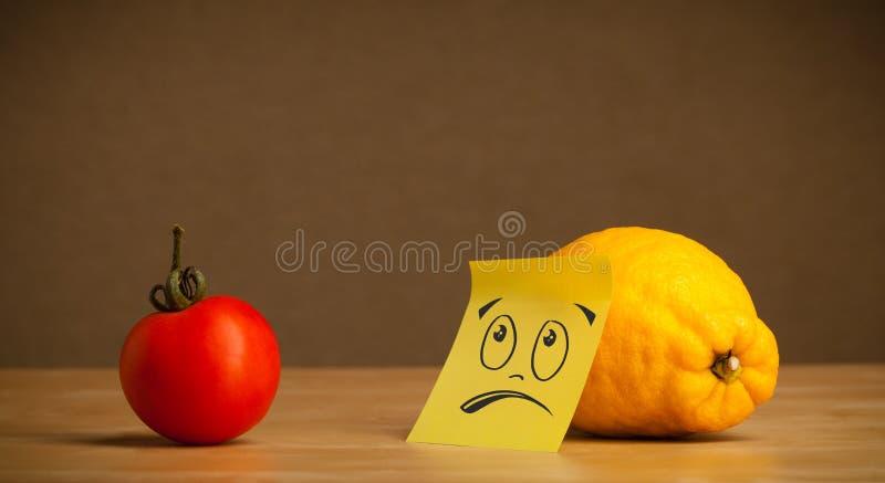 Λεμόνι με την κολλώδη post-it σημείωση που εξετάζει δυστυχώς την ντομάτα στοκ εικόνες με δικαίωμα ελεύθερης χρήσης