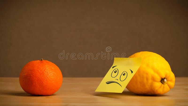 Λεμόνι με την κολλώδη post-it σημείωση που εξετάζει δυστυχώς το πορτοκάλι στοκ φωτογραφία με δικαίωμα ελεύθερης χρήσης