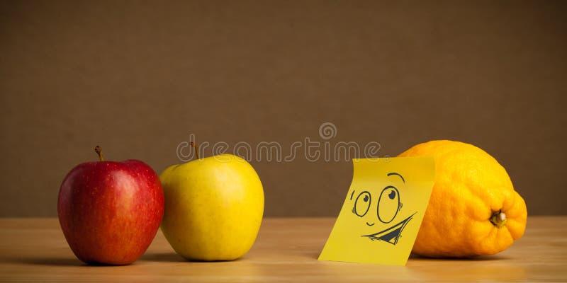 Λεμόνι με post-it τη σημείωση που εξετάζει περίεργα τα μήλα στοκ εικόνες με δικαίωμα ελεύθερης χρήσης