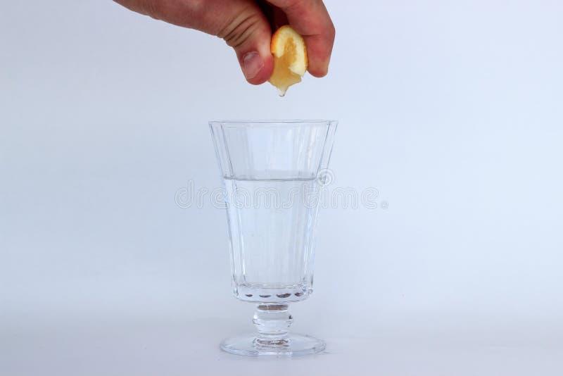 Λεμόνι συμπιέσεων του Aman στο νερό στο γυαλί στοκ εικόνες