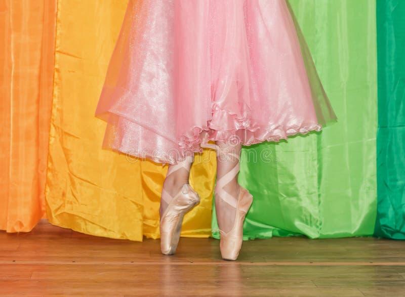 Λεπτά πόδια ενός ballerina ντυμένου στα παπούτσια Pointe, που στέκονται προς στοκ εικόνα