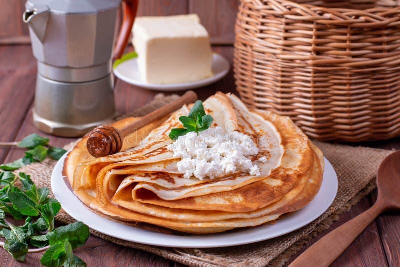 Λεπτές τηγανίτες στάρπης σε ένα άσπρο πιάτο Ο σωρός crepes, ρωσικό blin στοκ φωτογραφία