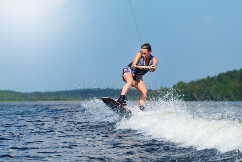 Λεπτή γυναίκα brunette που οδηγά wakeboard motorboat στο κύμα στη λίμνη στοκ φωτογραφία