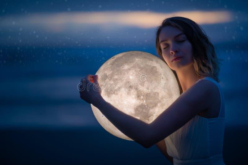 Λεπτή εικόνα ενός αγγέλου, ενός κοριτσιού με το φεγγάρι στα χέρια της στη νυχτερινή παραλία καλλιτεχνική φωτογραφία Παραμύθι και  στοκ φωτογραφία με δικαίωμα ελεύθερης χρήσης