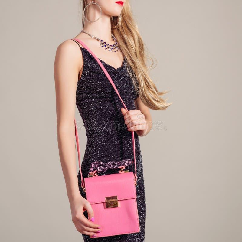 Λεπτή καθιερώνουσα τη μόδα γυναίκα στο φόρεμα βραδιού με τη ρόδινη τσάντα στα χέρια και το μοντέρνο περιδέραιο στοκ εικόνα