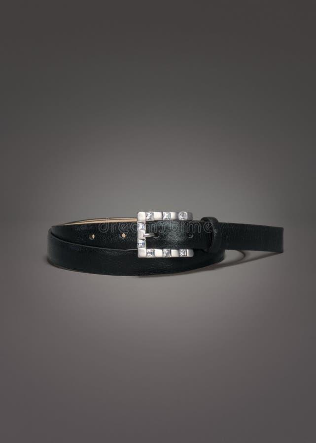 Λεπτή μαύρη ζώνη δέρματος με την πόρπη πολύτιμων λίθων στο γκρίζο υπόβαθρο κλίσης στοκ φωτογραφία με δικαίωμα ελεύθερης χρήσης