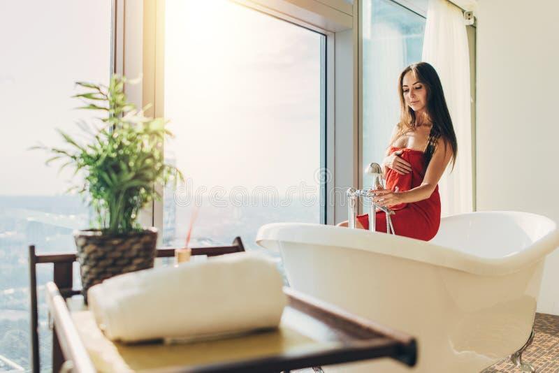 Λεπτή νέα γυναίκα στη συνεδρίαση πετσετών στην μπανιέρα στο πολυτελές λουτρό στοκ φωτογραφία με δικαίωμα ελεύθερης χρήσης